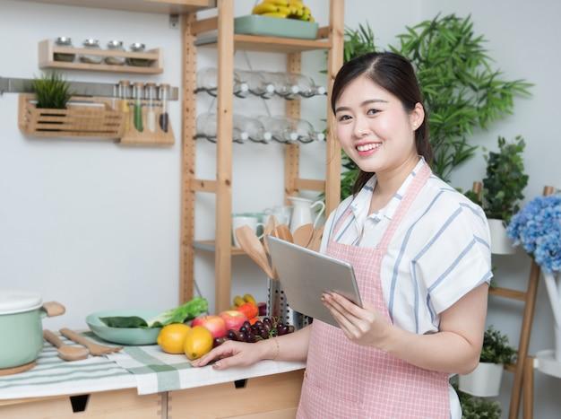 Glückliche asiatische frau, die rezepttablettenküche liest, die kochen zu hause liest