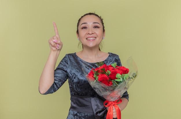 Glückliche asiatische frau, die strauß der roten rosen hält, die fröhlich zeigefinger zeigen, der neue idee hat, internationalen internationalen tag zu feiern, der über grüner wand steht