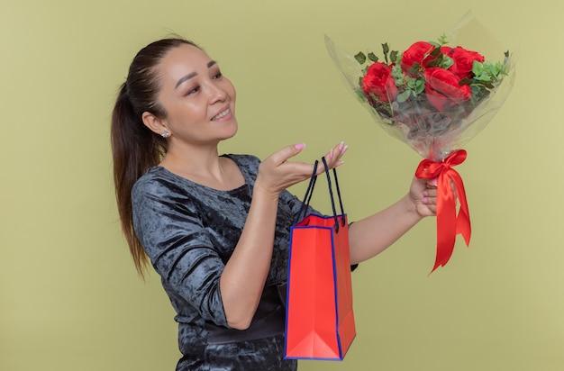 Glückliche asiatische frau, die strauß der roten rosen und der papiertüte mit dem geschenk hält, das fröhlich den internationalen frauentag steht, der über grüner wand steht