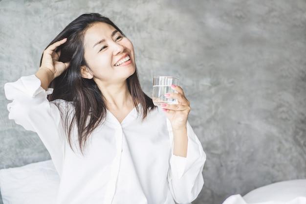 Glückliche asiatische frau, die süßwasser im bett trinkt