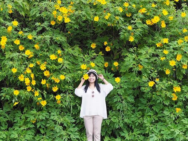 Glückliche asiatische frau, die über baumringelblume oder maxican sunflower hintergrund steht.