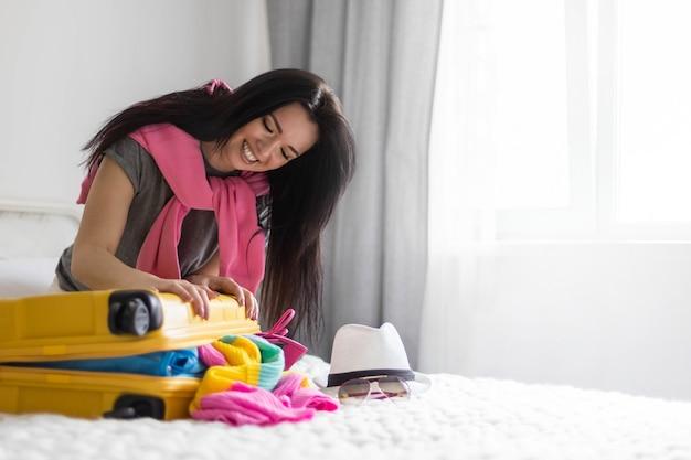 Glückliche asiatische frau, die versucht, gelben koffer voller verschiedener kleidungsaccessoires und schuhe zu schließen