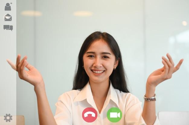 Glückliche asiatische frau, die video-chat-konferenz im büro verwendet
