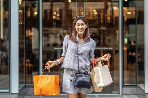 Glückliche asiatische frau, die vom kaufhaus heraus geht und die einkaufstasche hält