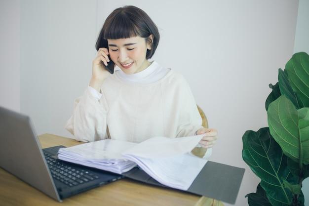 Glückliche asiatische frau, die von zu hause aus arbeitet. sie benutzt ein smartphone.