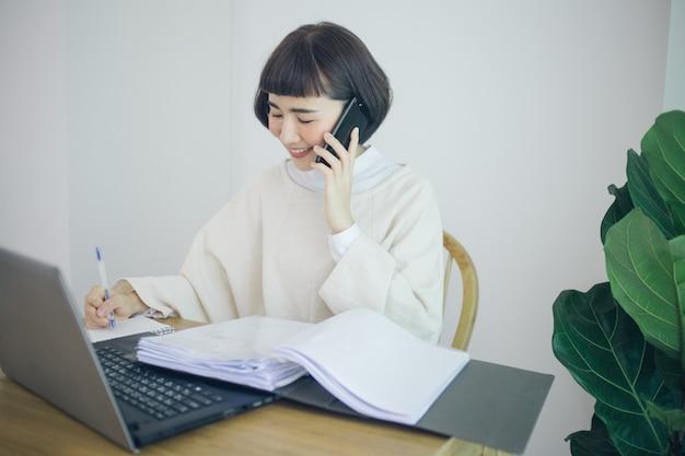 Glückliche asiatische frau, die von zu hause aus arbeitet. sie benutzt smartphone, taplet und handschrift.