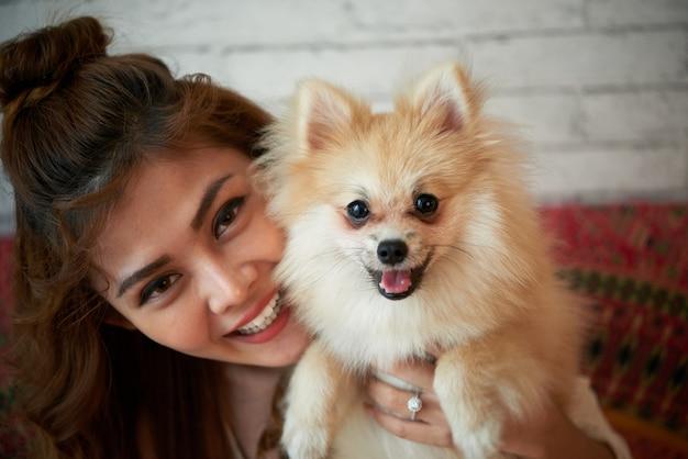 Glückliche asiatische frau, die zu hause mit kleinem schoßhund aufwirft