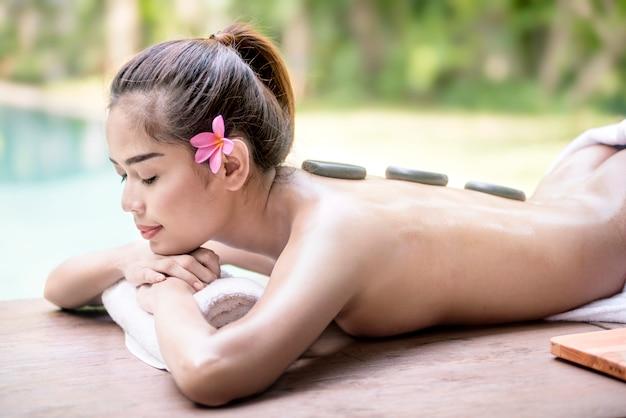 Glückliche asiatische frau, die zurück heiße steinmassage auf seinem genießt