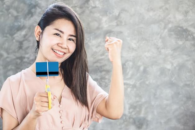 Glückliche asiatische frau frei von der schuldhand, die kreditkarte durch scheren mit lächelndem gesicht schneidet