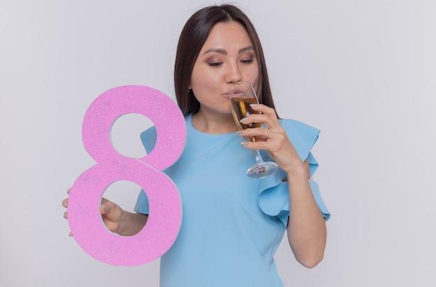 Glückliche asiatische frau im blauen kleid hält nummer acht aus pappe und glas champagnertrinken und feiert den internationalen frauentag, der über weißer wand steht