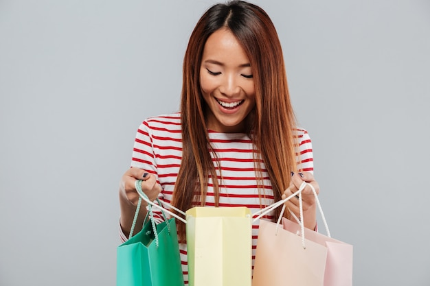 Glückliche asiatische frau im pullover, der in paketen schaut