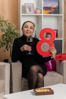 Glückliche asiatische frau im schwarzen kleid sitzt auf einem stuhl mit glas wein, das nummer acht hält, das fröhlich im hellen wohnzimmer lächelt, das internationalen marsch der frauentag feiert