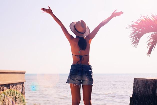 Glückliche asiatische frau in der bikinioberseite und in den kurzen hosen auf dem strand. sommerkonzept