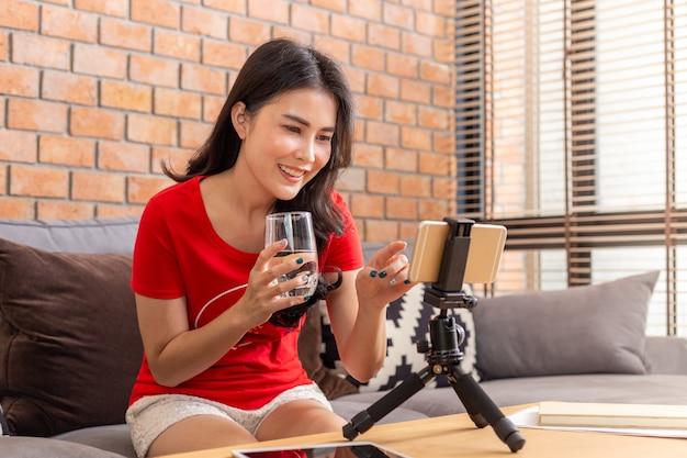 Glückliche asiatische frau in der freizeitkleidung, die glas wasser hält, während sie sich mit online-freunden verbindet