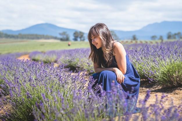 Glückliche asiatische frau in einem langen blauen kleid posiert auf dem lavendelfeld