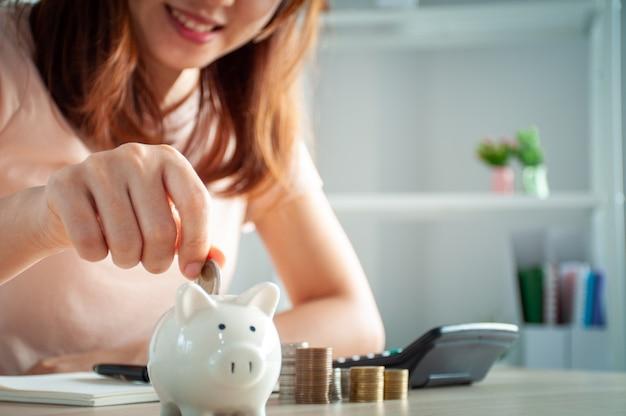 Glückliche asiatische frau legt geld in ein sparschwein
