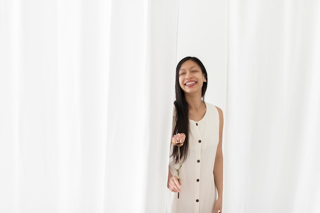 Glückliche asiatische frau mit einer trockenen rosa pfingstrosenblume in einer hand unter dem weißen vorhang