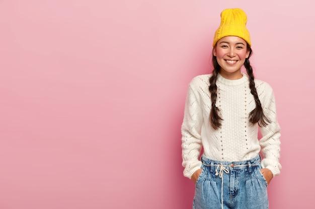Glückliche asiatische frau mit zartem lächeln, hält beide hände in den taschen auf jeans, trägt gelben hut, weißen pullover, hat zwei zöpfe posiert über rosiger wandleerfläche