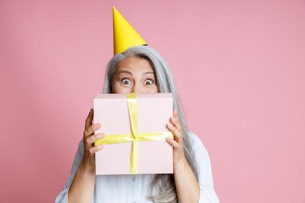 Glückliche asiatische frau mittleren alters hält geschenkbox in der nähe des gesichts auf rosa hintergrund im studio