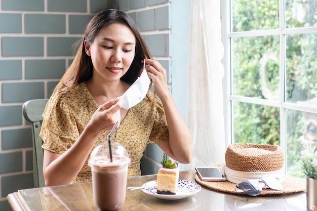 Glückliche asiatische frau nehmen medizinische maske vor dem essen ab