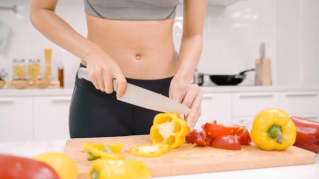 Glückliche asiatische frau schneidet viel paprika und bereitet zutat für die zubereitung von speisen in der küche zu