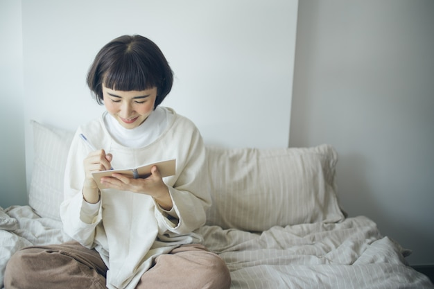 Glückliche asiatische frau schreibt im schlafzimmer. sie arbeitet von zu hause aus.