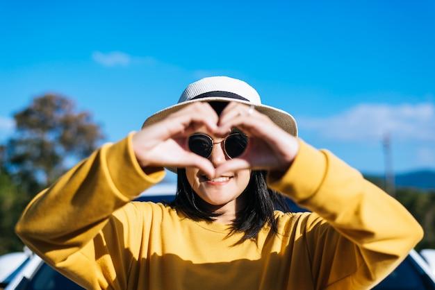 Glückliche asiatische frau stehend und zeigt handherzform an der natur, glücklich und lächelnd, positives denken, rückansicht