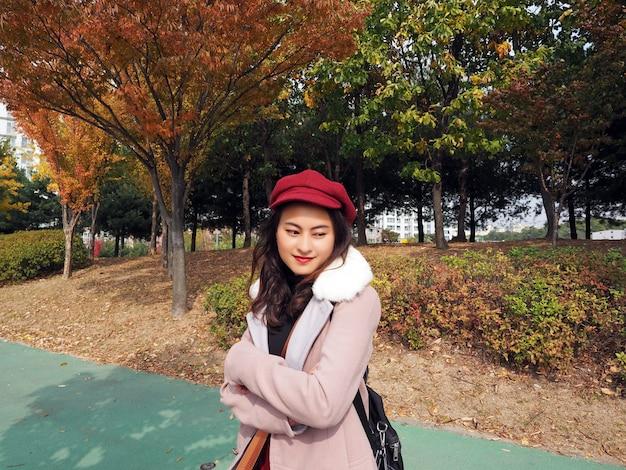 Glückliche asiatische frau trägt rosa wintermantel und rote kürbisförmige kappe, die im herbst auf grüner straße steht