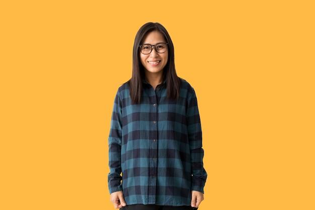Glückliche asiatische frau und lächeln drückt im allgemeinen das glück aus, fühlt sich freudig an, isoliert auf gelbem hintergrund