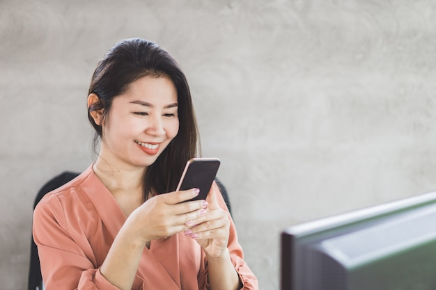 Glückliche asiatische frau verdienen geld online vom intelligenten telefon