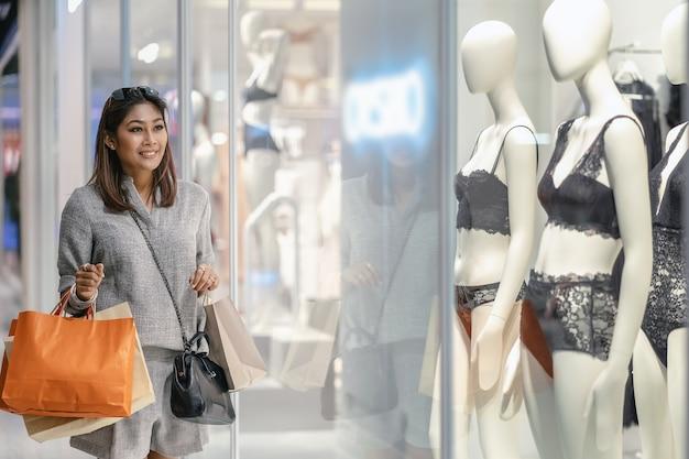 Glückliche asiatische frau, welche die einkaufstasche hält und nach neuer modeschutzkleidung sucht