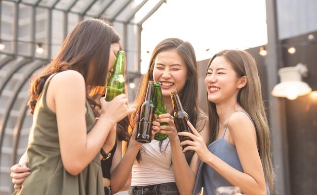 Glückliche asiatische frauen, die eine flasche bier halten, plaudern zusammen.