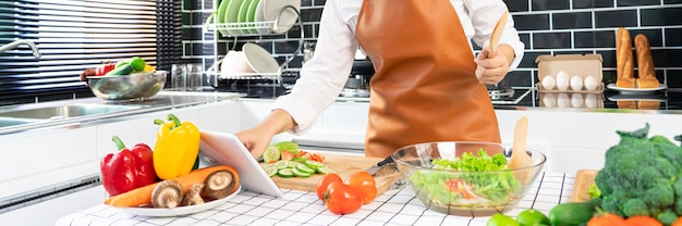 Glückliche asiatische frauen, die gesundes essen kochen, während rezept auf digitalem tablett suchen