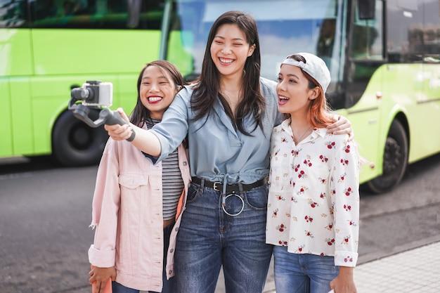 Glückliche asiatische frauen, die video am stadtbusbahnhof machen