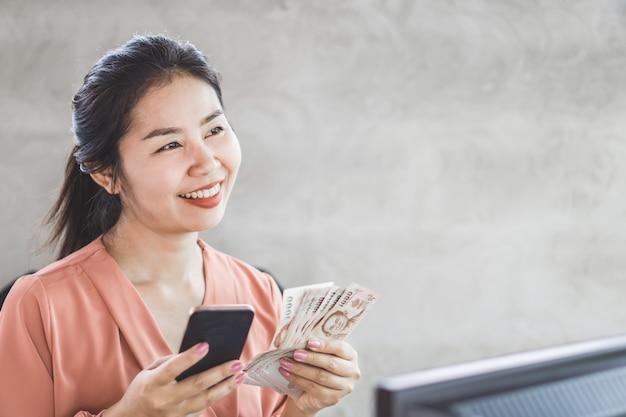 Glückliche asiatische frauenhand, die intelligentes telefon und banknoten hält