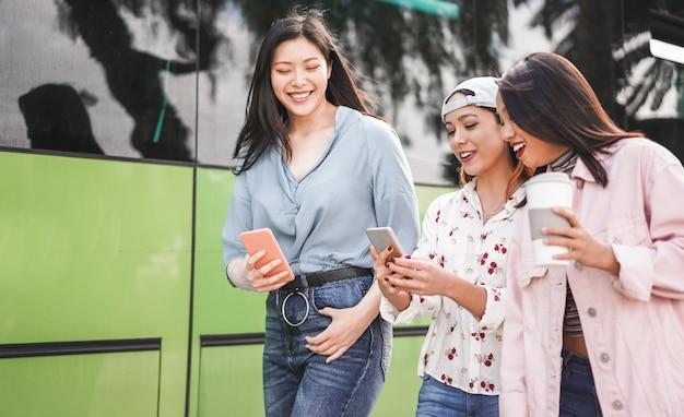 Glückliche asiatische freunde, die smartphones am busbahnhof verwenden. junge studenten, die spaß mit technologietrends nach der schule haben