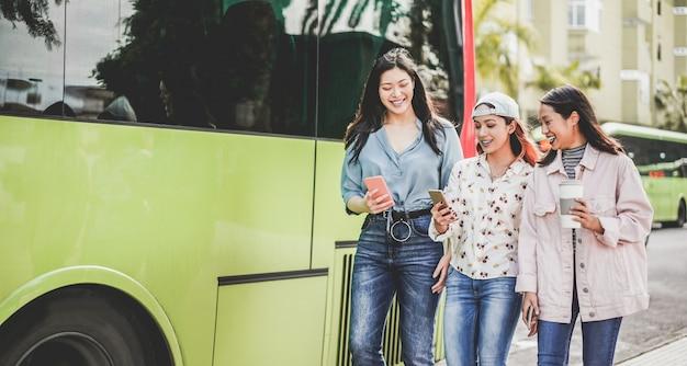 Glückliche asiatische freunde, die smartphones am busbahnhof verwenden. junge studenten, die spaß nach der schule im freien haben