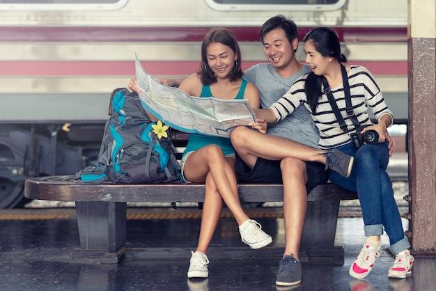 Glückliche asiatische freunde gruppieren die sitzende planung für reisende zusammen an der bahnstation und schauen die karte.