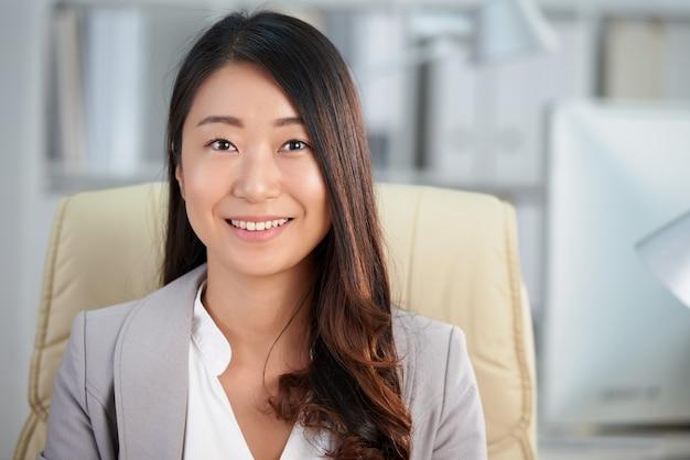 Glückliche asiatische geschäftsdame, die im büro und im lächeln sitzt