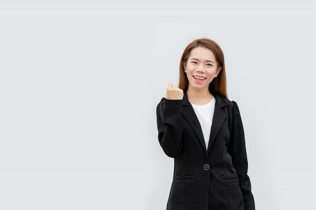 Glückliche asiatische geschäftsfrau bewaffnet sich im schwarzen anzug lokalisiert auf weißer farbe