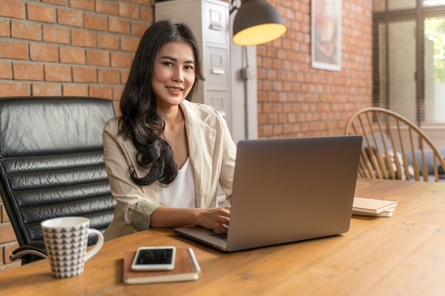 Glückliche asiatische geschäftsfrau, die an der kamera lächelt, während sie ihren computer während der arbeit von ihrem haus benutzt