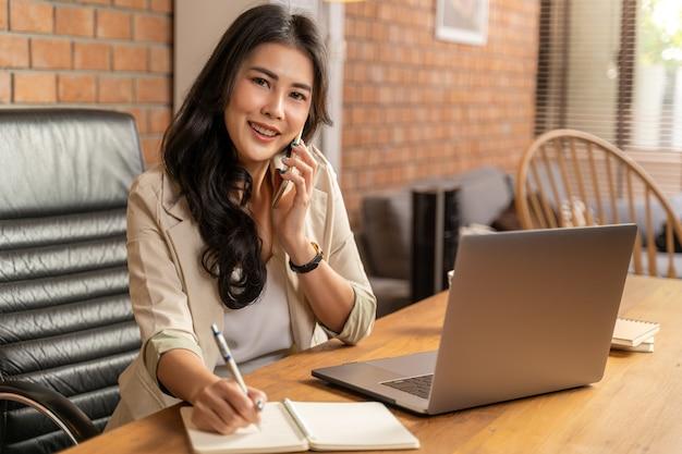 Glückliche asiatische geschäftsfrau, die das telefon annimmt, während sie einen computer während der arbeit von ihrem haus benutzt