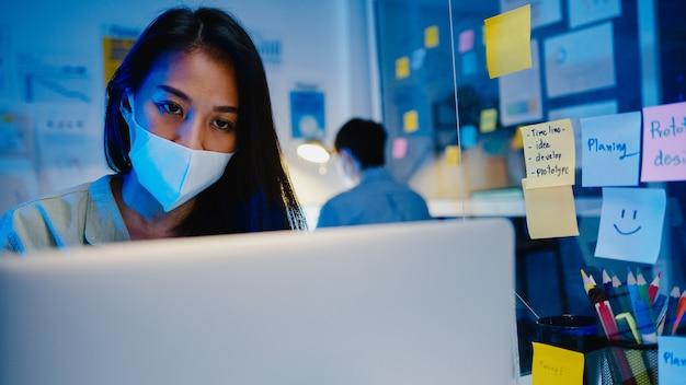Glückliche asiatische geschäftsfrau, die medizinische gesichtsmaske für soziale distanzierung in neuer normaler situation zur virenprävention trägt, während laptop zurück bei der arbeit in der büronacht verwendet. leben und arbeiten nach dem coronavirus.