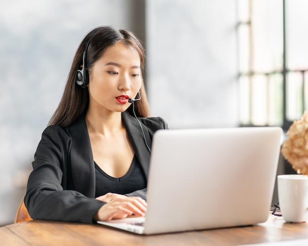 Glückliche asiatische geschäftsfrau im headset, das durch telefonkonferenz und video-chat auf laptop im büro spricht