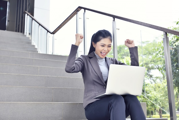 Glückliche asiatische geschäftsfrau mit laptopfunktion
