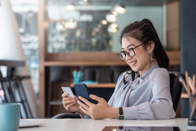 Glückliche asiatische geschäftsfrau zahlen online mit handy im büro.