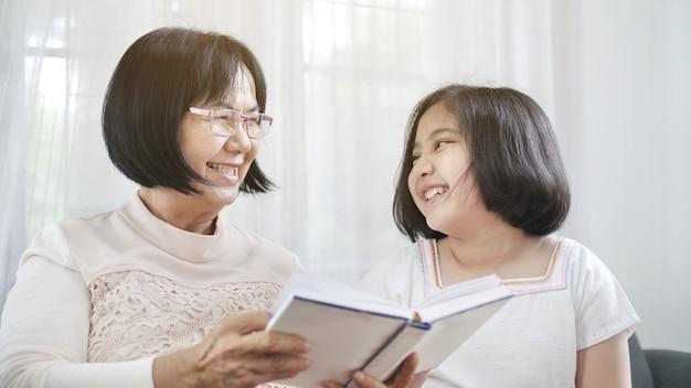 Glückliche asiatische großmutter und reizendes mädchenlesebuch zusammen zu hause