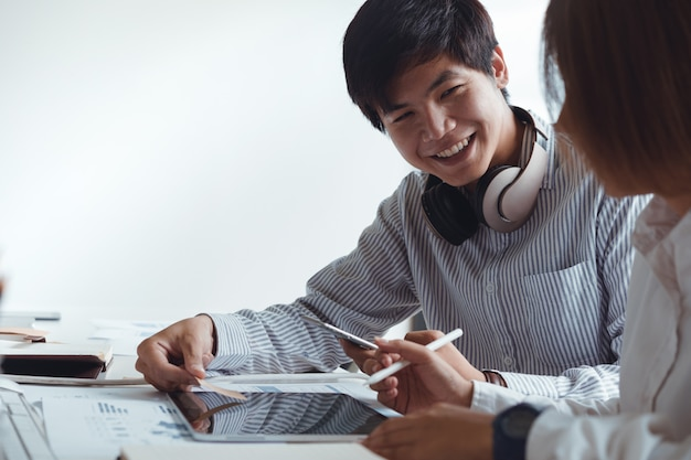 Glückliche asiatische hochschulstudenten, die zusammen an der digitalen tablette, bereitend für prüfungen sitzen und arbeiten.