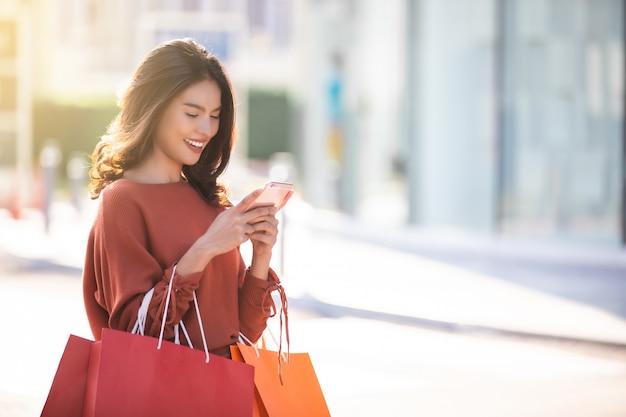 Glückliche asiatische hübsche frau, die einkaufstaschen hält, während smartphone verwendet