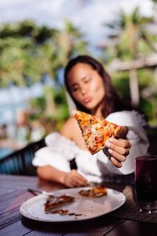 Glückliche asiatische hübsche frau, die hungrig ist, pizza am sonnenunterganglicht des sonnigen tages im restaurant im freien weiblich zu haben, das essen genießt, das spaß am mittagessen hat
